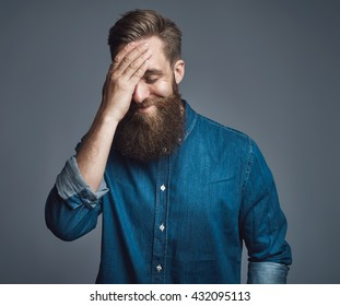 Single grinning handsome man with long beard in blue denim buttoned shirt and embarrassed expression over gray background