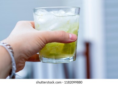 Single hand holding a Brazilian caipirinha.  Man toasting and saying cheers.