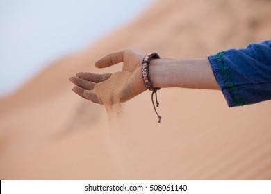 Single hand holding sand in desert let it running through fingers, Muine sand dunes, Vietna