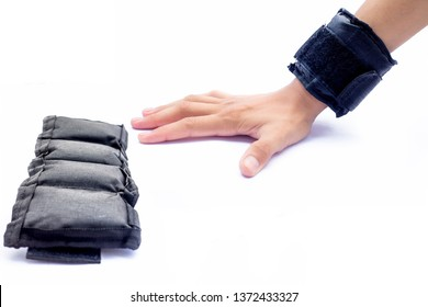 Single hand isolated on white wearing black colored wrist weight and another one on the surface.