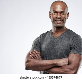 Single handsome fit grinning young Black adult with shaved head and folded muscular arms over gray background with copy space