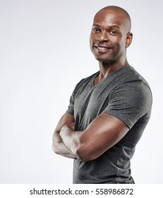 Single handsome muscular Black man with shaved head, folded arms and cheerful expression