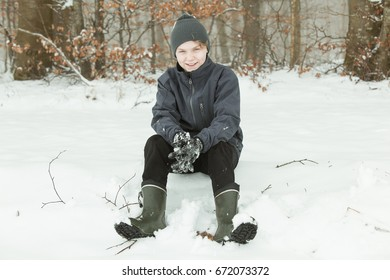 Single handsome smiling teen in hat and jacket sitting in the snow near the woods. He is surrounded by twigs and leaves in background.