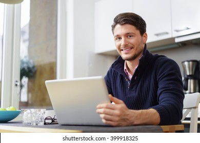 Single handsome young bearded smiling man behind open laptop on table in bright kitchen with large window