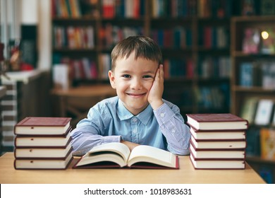 Single happy boy at the desk in the library enjoy books. Front image with boy keeping left hand on the cheek . European boy explore books. Pupil loves lecture, education, preparing for school.