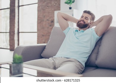 Single happy young man is relaxing on the sofa at home. He is dreaming about vacation, that is coming