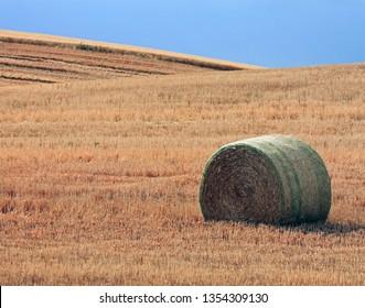 Single Hay Bale in a Farm Field under a Blue Sky
