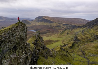 Single hiker on top of mountain in rugged volcanic landscape around Quiraing, Isle of Skye, Scotland