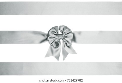 Single silver bow with horizontal ribbons for Christmas decorations of boxes on white background