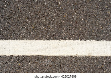 Single horizontal white traffic line painted on a grey tarmac road. Copy space area