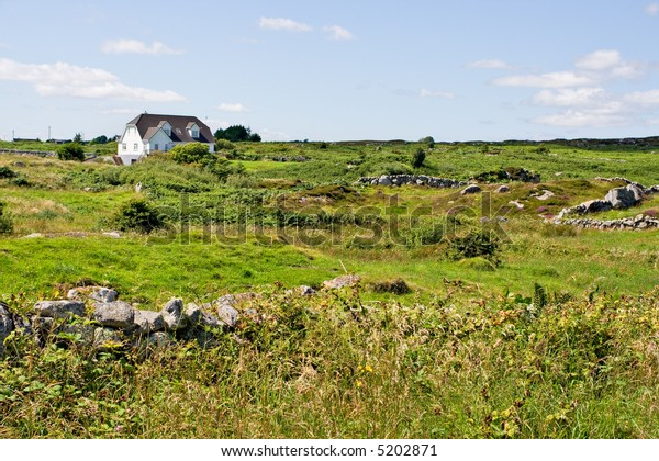 A single house in a green field. Location is Galway, Ireland.
