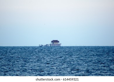 A single house. In the middle of the sea. Detached house in the middle of the sea