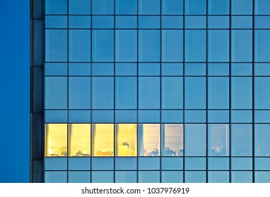 A single illuminated office window in a modern steel and glass bank building. Working late in an office tower.