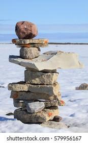 A single Inukshuk (Inuksuk) near the community of Igloolik, Nunavut with snow in the background