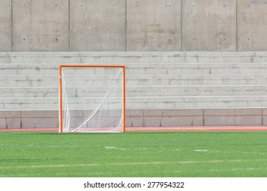 A single lacrosse goal on a turf field with a cement wall background