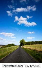 Single lane country road through countryside and farmland