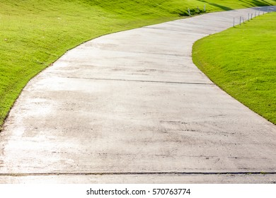 The single lane and curved cement pathway through in green golf course.
