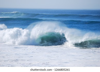 A single large curling wave crashing amongst a line of waves in the Pacific Ocean near Carmel, California. White spray, no rocks, open ocean, surf area, all ocean.