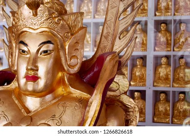 Single large golden warrior buddha statue in the foreground with a wall of ten thousand golden buddha statues in the background at the City of 10,000 Buddhas in Talmage (Ukiah) California.