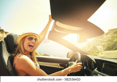 Single laughing or celebrating young woman with hat and sunglasses driving her convertible top automobile on bright sunny day near ocean