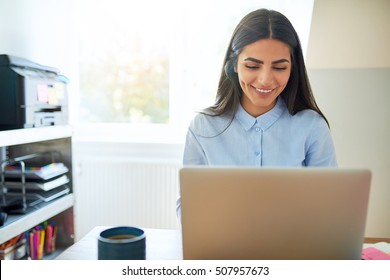 Single laughing young Indian woman beside printer on shelf and wearing long hair while seated in front of laptop computer in bright room