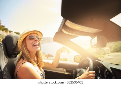 Single laughing young woman with hat and sunglasses driving her convertible top automobile on bright sunny day