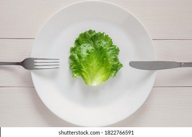 single lettuce leaf on the plate with fork and knife, detox mono diet for weight loss
