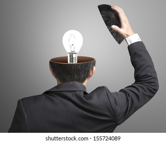 Single lighting lamp inside businessman head in gray background