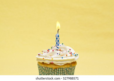single lit candle on top a cupcake isolated on yellow