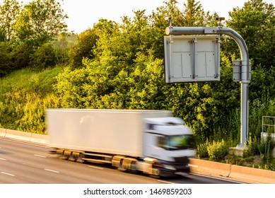 single lorry truck on uk motorway road under information display at sunset