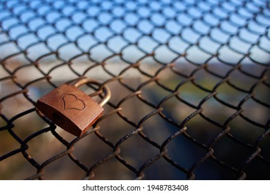 Single Lovelock ( Liebesschloss ) fixed to an old rusty wire mesh fence, heart shape can be seen on the weathered metal. Nice blue sky. Closeup.