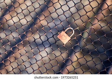 Single Lovelock ( Liebesschloss ) fixed to an old rusty wire mesh fence, heart shape can be seen on the weathered metal. in the background there are rails of a railroad. Top view.