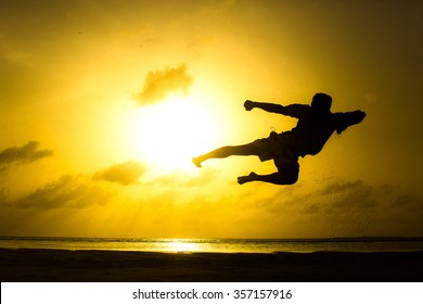 Single man does martial arts on the beach during sunset time. Wushu.