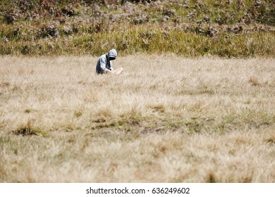 Single man in hoodie sitting alone in grass field, mysterious lonely guy
