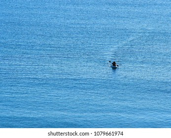 Single man paddling a kayak in the middle of blue sea ocean