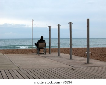 Single man sitting on a chair looking at the sea