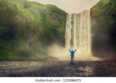 Single man standing near Scogafoss waterfall in Iceland and spread his hands. Travel summer nordic concept.
