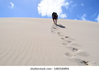 single man walks through desert leaving footprints behind on sand hill
