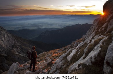 Single man watching the dramatic sunset in the mountains. Colorful landscape. Grintovec, Alps, Slovenia.