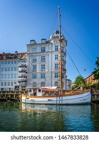 Single masted wooden sailing boat in the canal in the Nyhavn district of Copenhagen, Denmark on 18 July 2019