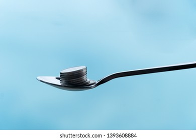 single metal teaspoon with silver coin money pile for food capitalism business concept financial background