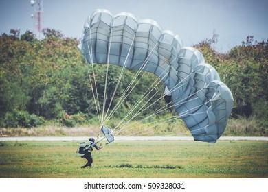 Single military parachute jumper on a blue wing parachute on blue sky background