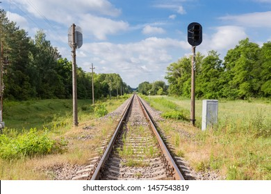 Single modern railroad tracks with concrete sleepers and railway traffic lights among the forest