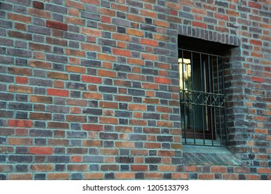 A single modern window with a grate on a long old brick wall with crosses