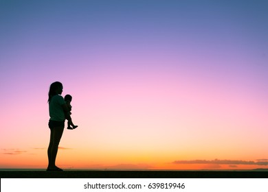 Single mother holding her baby child watching the sunset.