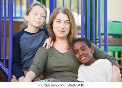 Single mother sitting with cute male children at park together