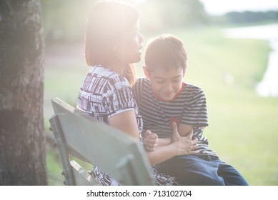 Single mother with son sitting together in the park sunset time