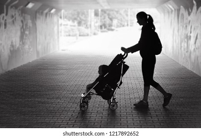 Single mother walking in city tunnlle baby in stroller. People d