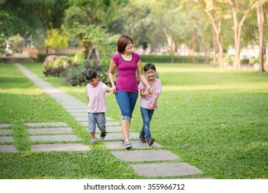 single mother walking in the park with sons