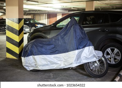 Single motorcycle is in warm underground parking garage covered with a tent